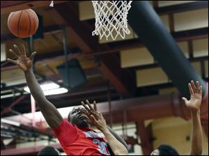 Bowsher's Mark washington (30) shoots against Scott's Jay Wells (42) and Chance Hawkins (20).