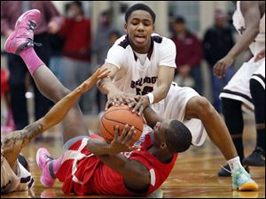 Scott's Chris Harris (5), left, and Chris Darrington (32), top, battle  Bowsher's Nate Allen (23) for a loose ball.