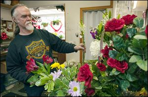 Adrian Brazier, who, with his wife, Jessica, owns Gloria's Florist in Elmwood Park, N.J. tends to his arrangements.