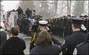 Firefighters salute as the casket holding Toledo firefighter Private James Dickman arrives at Oakland Cemetery in Sandusky after a funeral service that drew more than 700 to The Chapel on Galloway Road near Sandusky.