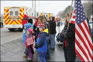Kim Cowie of Sandusky, with the U.S. flag, joins others in front of Perkins Township Fire Station 2 to wait for the procession as it moves toward the cemetery.