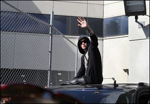 Singer Justin Bieber waves from atop an SUV as he leaves the Turner Guilford Knight Correctional Center, in Miami, last week.
