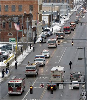 The funeral procession, which was met throughout the route at every overpass by other fire trucks, police cars, or other emergency vehicles, heads down Monroe Street in downtown Toledo.