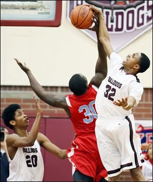 Scott's Chris Darrington, right, blocks a shot by Bowsher's Mark Washington. Darrington scored 17 points. Washington had seven.