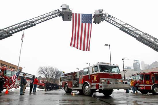 A-fire-truck-passes-under-the-flag-during-the-procession