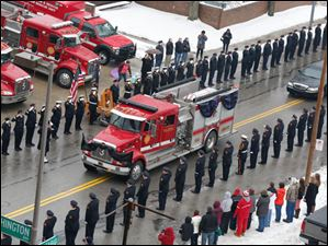 Toledo Fire Department members salute as fire truck carrying the flag-draped casket passes Station No. 5 on North Ontario Street.