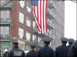 Toledo firefighters put up the large American flag at the corner of N. Ontario and Washington streets.