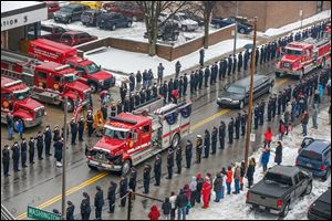 Engine 3 from the Toledo Fire Department, draped in black and purple bunting, carries Pvt. Stephen Machcinski's coffin past Station 5 on North Ontario Street as the rest of the funeral procession follows.