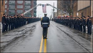 Honor Guard Jeffrey Koenigseker gives commands as firefighters stand at attention during the funeral procession for Toledo firefighter Stephen Machcinski as it passes by Station 5 in downtown Toledo.