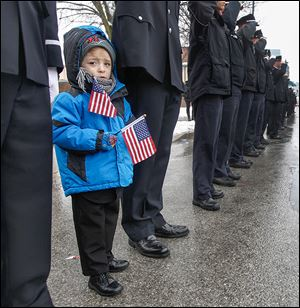 Caden Quinn, 4, joins his father, Pvt. Gary Quinn of the Toledo Fire Department, as the procession passes Station 5. Private Machcinski was a 15-year member of the department.