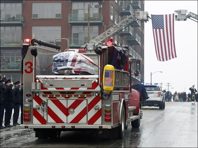 Toledo Firefighters salute as the casket of Toledo Firefighter Stephen Machcinski passes by Station 5 in Downtown Toledo.
