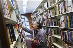 Justine Keeler, 78, browses the collection at the Sylvania Branch library. The branch, which was built in the 1950s, was expanded in 1989, but has not undergone any sort of major change to its layout since.