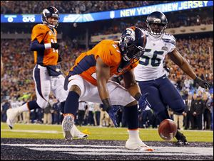 Denver Broncos running back Knowshon Moreno reaches for a loose ball after the snap sailed passed Peyton Manning, left, during the first quarter in Super Bowl XLVIII on Sunday in East Rutherford, N.J. The play resulted in a safety for Seattle.