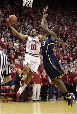 Indiana guard Evan Gordon, left, holds off Michigan guard Caris LeVert on Sunday in Bloomington, Ind.