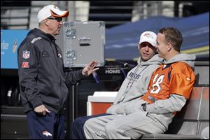 Denver Broncos head coach John Fox, left, talks with quarterback Peyton Manning (18) on Saturday in MetLife Stadium in East Rutherford, N.J.