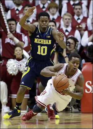Indiana guard Yogi Ferrell, right, slips under pressure from Michigan guard Derrick Walton, Jr.
