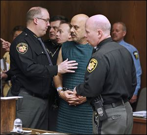Sheriff's deputies try to keep Ray Abou-Arab, who is dressed in a suicide smock, from talking to people in the courtroom following his arraignment.