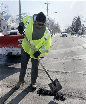 Debbie Gray, who works for the city's Department of Streets, Bridges, and Harbor, patches a pothole on Douglas Avenue near Westbrook Drive in West Toledo.