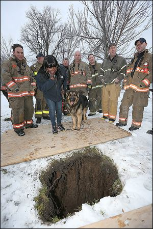 Buffalo, N.Y. Rescue 1 firefighter Michael Paveljack, left,  Mattie Moore, second from,left, and her dog Mack stand by the sink hole.
