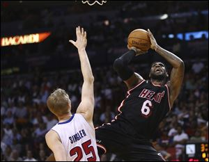 Detroit Pistons' Kyle Singler (25) tries to block Miami Heat's LeBron James (6) during the first half.