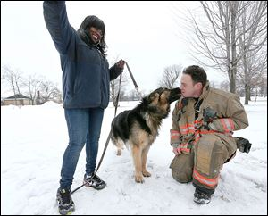 Rescue 1 firefighter Michael Paveljack, right, gets a kiss from Mack, the dog he rescued.
