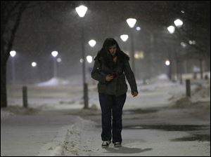 Elise Clark, a psychology major, walks to her car at the University of Toledo. She is going home to Addison, Michigan, a 90-minute drive in a snowstorm.