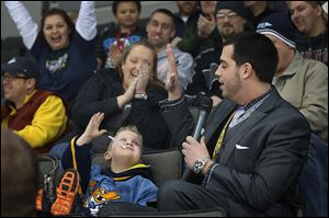 Walleye announcer Anthony Bellino, right, high fives Connor Wright, 4, during a recent game. The 2010 Bowling Green State University graduate is in his first season with the Walleye.