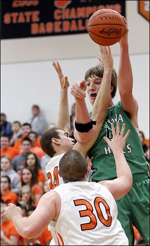 Ottawa Hills' R.J. Coil passes the ball against Gibsonburg's Andy Burmeister, center, and Andrew Cantrell. Coil scored 20 points.