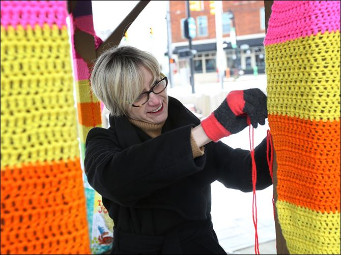 n4yarn-5 Michelle Atkinson puts the finishing touches Tuesday on the crocheted yarn enveloping the posts of the gazebo near the downtown. Ms. Atkinson spearheaded the project, organized with the Sylvania Community Arts Commission's blessing. Ms. Atkinson said she hopes to make it an annual event.