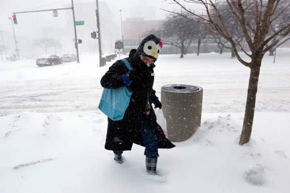 Julie-Bellman-wearing-a-penguin-hat-trudges-through-accumulating-snow-as