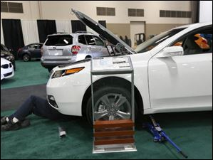An auto stager gets under the 2014 Acura TL AWD.