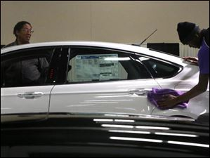 Eric Sauls, the field supervisor with the Ondi Group, right, led a team of people in polishing the 2014 Ford Fusion Hybrid.