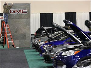 A GMC sign receives a final polishing as Ford's cars are lined up.