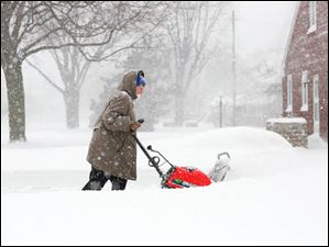 anice Mossing clears the driveway of her neighbor's home near her home on Lehman near 288th Street.