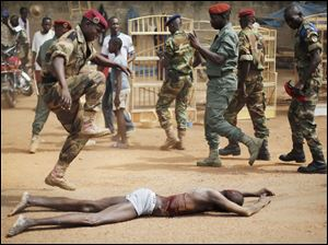 A  FACA (Central African Armed Forces) officer jumps on the lifeless body of a suspected Muslim Seleka militiaman moments after Central African Republic Interim President Catherine Samba-Panza addressed the troops.