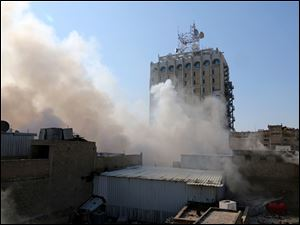 Smoke rises after a parked car bomb went off at a commercial center in Khilani Square in central Baghdad, Iraq, today.