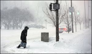 A pedestrian crosses Jackson Street at North Huron Street during a snowstorm today.