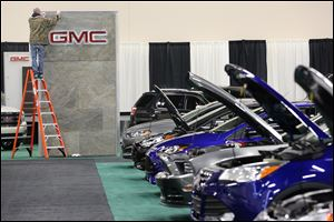 The GMC sign receives a final polishing as part of the preparation for today's opening of the Toledo Auto Show at SeaGate Convention Centre. A line of Ford vehicles sits at the right.