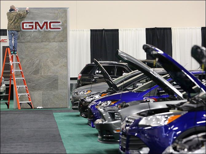 b5show-2 The GMC sign receives a final polishing as part of the preparation for today's opening of the Toledo Auto Show at SeaGate Convention Centre. A line of Ford vehicles sits at the right.