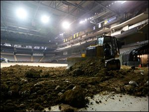 Workers spread dirt on the Hunting Center Floor in preparation for The Professional Bull Riders event on Feb. 6, 2014.