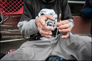 A drug addict prepares a needle to inject himself with heroin in the Skid Row area of Los Angeles. Officials said more than 660,000 Americans used heroin in 2012 — nearly double the number reported five years earlier. Overdoses and emergency-room visits have skyrocketed, they said.