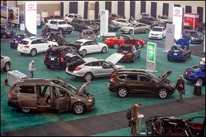 People check out the new models on display at the 2014 Greater Toledo Auto Show on Thursday. There are  25 brands, 126 ve­hi­cles, and 14 mo­tor­cy­cles to investigate.