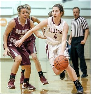 Rossford's Julie Hotz drives past Genoa's Ciara Albright. Hotz led the Bulldogs with 15 points. Albright led all scorers with 26 points, surpassing 1,000 for her career.