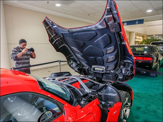 b6autoshow-1 James Watkins, 16, of Toledo photographs a Dodge Viper on the opening day of the auto show.