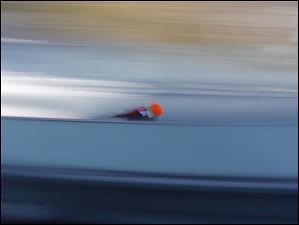 In this slow shutter speed photo an unidentified athlete starts an attempt during the men's normal hill ski jumping training Friday.