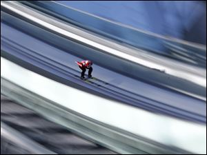 In this slow shutter speed photo Switzerland's Simon  Ammann starts an attempt during the men's normal hill ski jumping training.