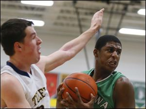 Ottawa Hills basketball player Ellis Cummings (44) steals a rebound from Toledo Christian basketball player Nathan Walton (22).