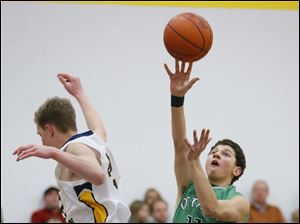 Ottawa Hills basketball player Hunter Sieben (11) is fouled by Toledo Christian basketball player Ian Gibson (42).