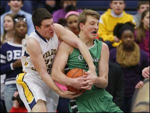 Ottawa Hills basketball player R. J. Coil, right, and Toledo Christian basketball player Nathan Walton (22), battle for a rebound.