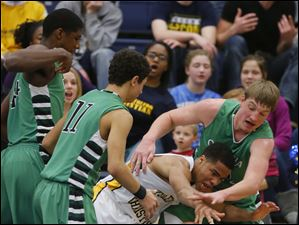 Ottawa Hills basketball player R.J. Coil (40) and Toledo Christian basketball player Garshawn Paynther (3) battle for the ball as Ottawa Hills players Ellis Cummings (44) and Hunter Sieben (11) close in.